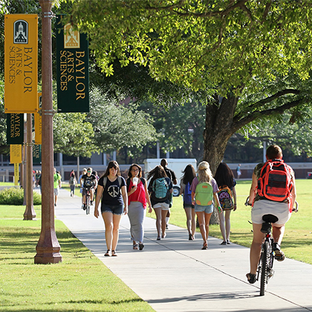 A bunch of students with backpack walking down a campus path next to trees and pole with sign reading Baylor University