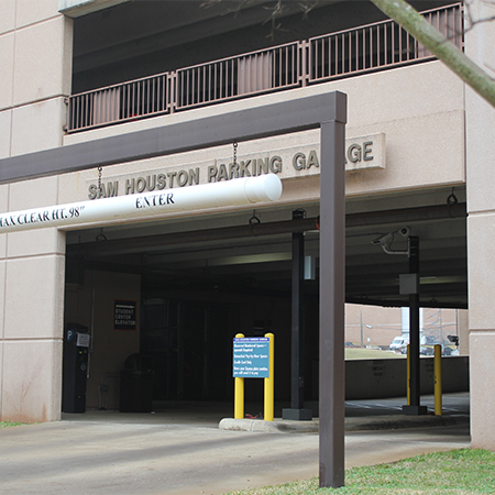 "Entrance to a parking garage with poles and clearance signs and reading ""Sam Houston Parking Garage"" on top"