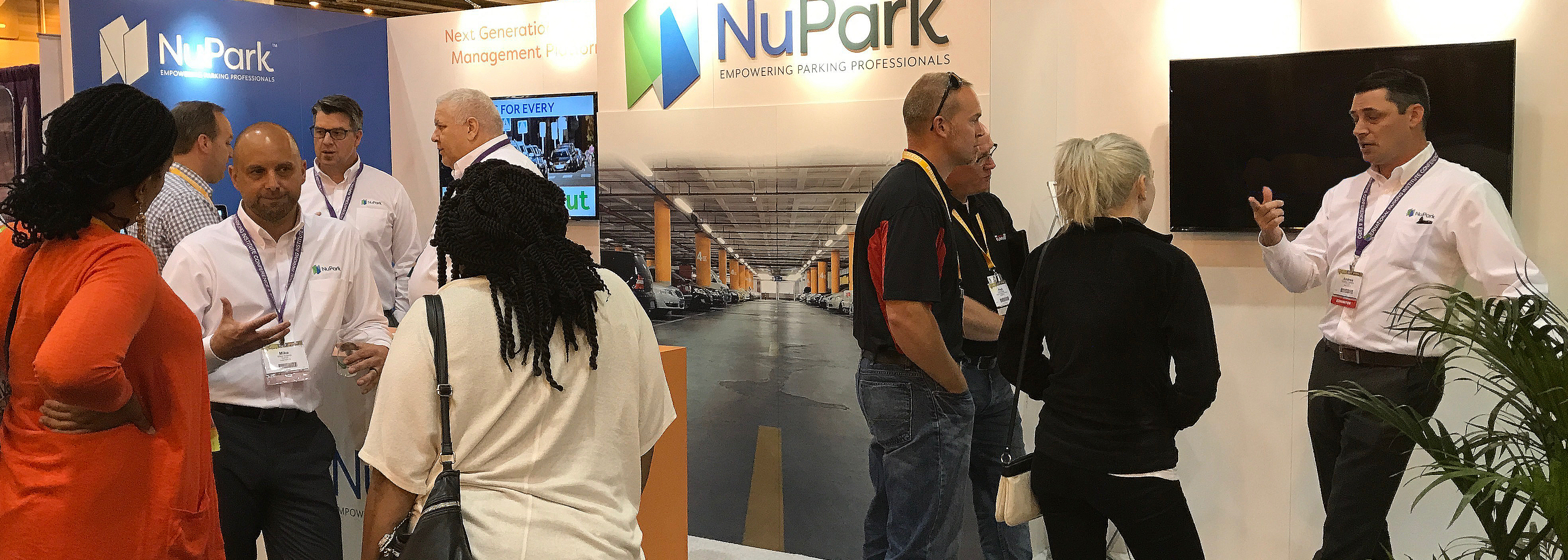 a group of NuPark staff dressed in white talking to groups of people around a booth area