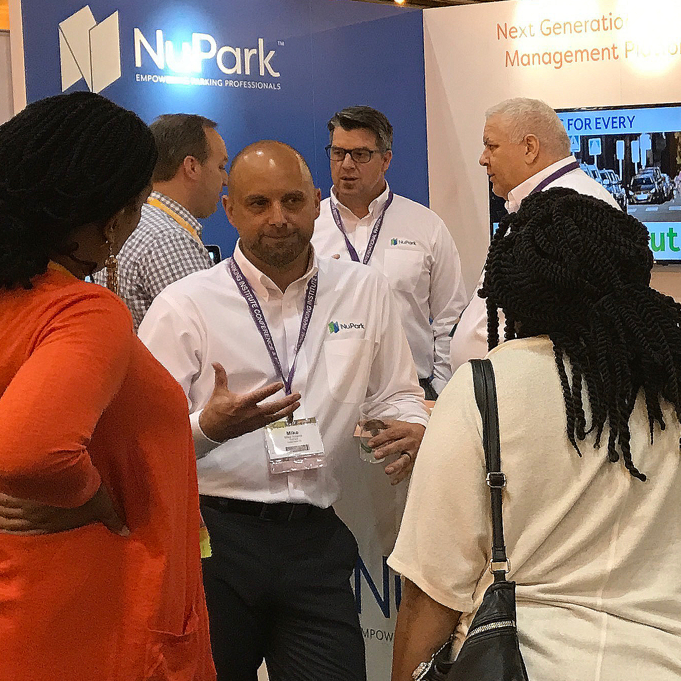 man in white shirt and black pants speaking to two ladies in white and orange clothes with men in the background talking with NuPark sign in the. back