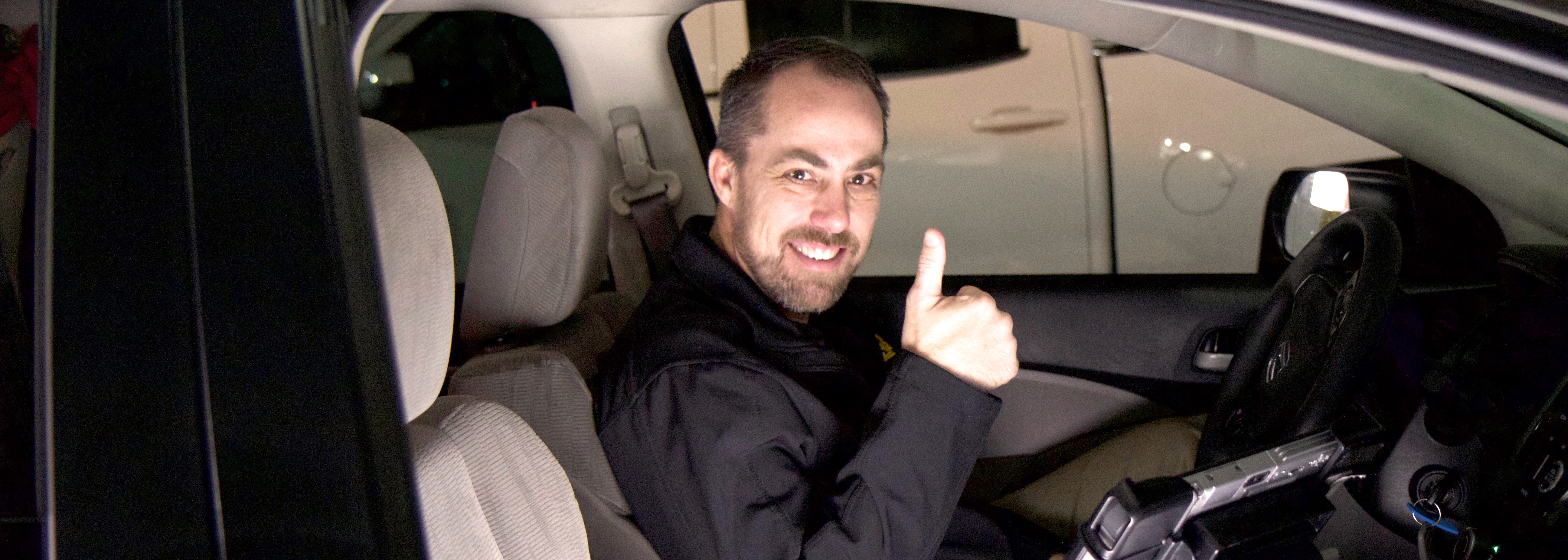 Baylor Parking director giving thumbs up inside a car
