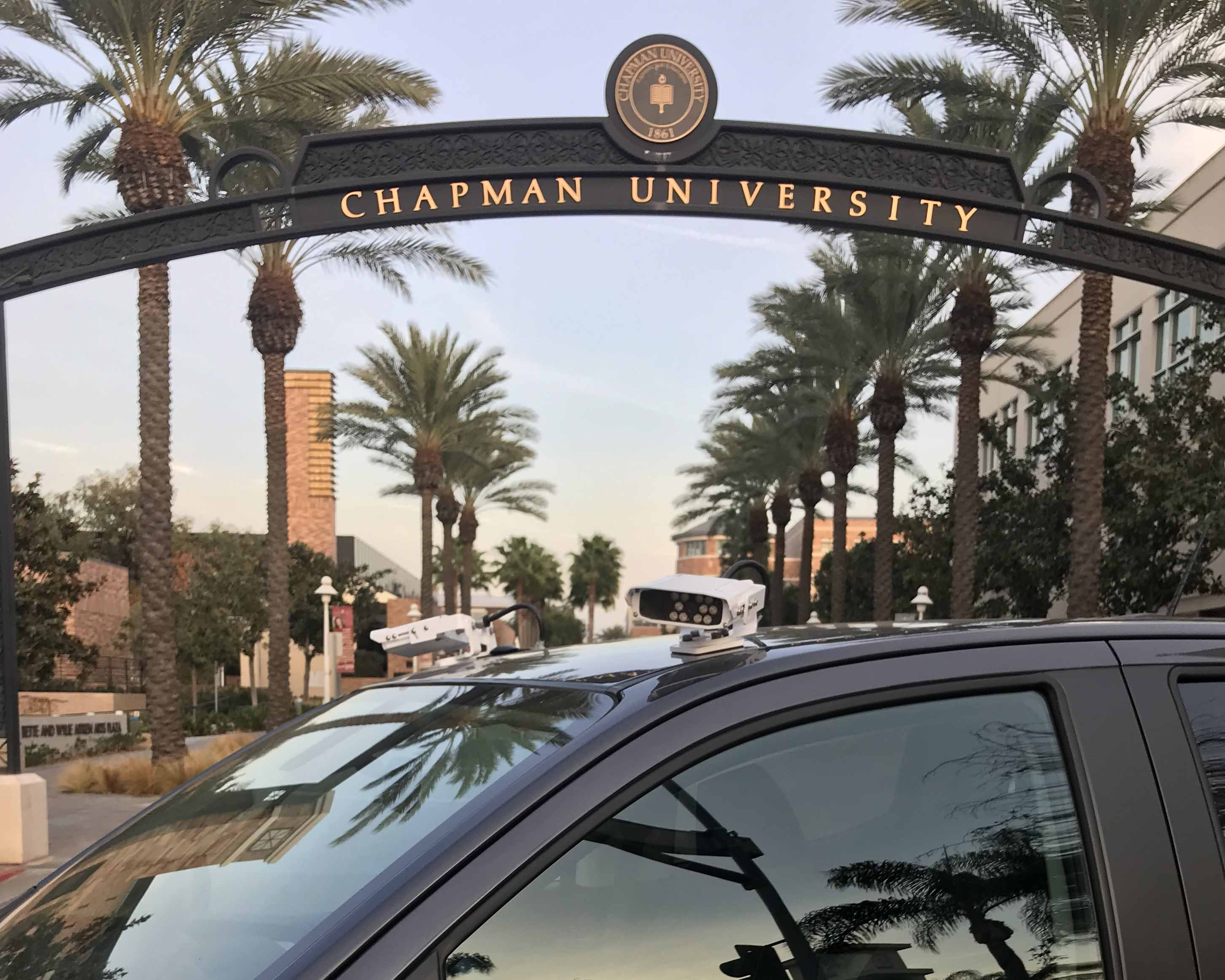 black Enforcement vehicle with two LPR cameras  in front of Chapman University entrance gate