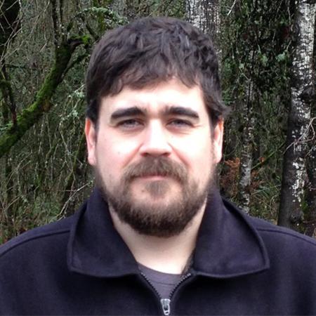 Bearded man headshot in black fleece with green behind.